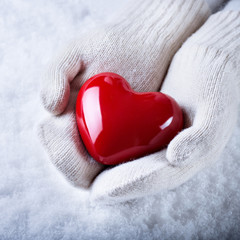 Female hands in white knitted mittens with a glossy red heart on a snow background.  Love and St. Valentine concept