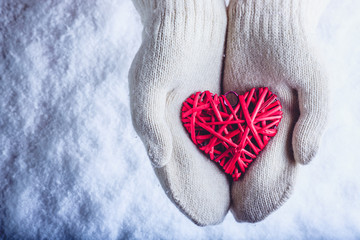 Female hands in white knitted mittens with entwined vintage romantic red heart on snow background. Love and St. Valentine concept.