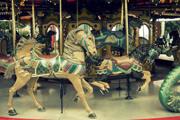 Retro image of decorated horses on old-time carousel