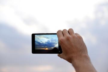 Man using smart phone for taking photo of beautiful sky