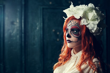 Portrait of beautiful young redhead woman with Halloween sugar skull makeup looking aside. Close up. Dark green backgraund. Copy space, free text.