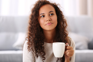 Close up portrait of pretty young woman drinking coffee in the room