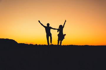 couple jumping joyfully at sunset in summer