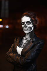 Young woman with Halloween makeup is standing on the street  . Street portrait