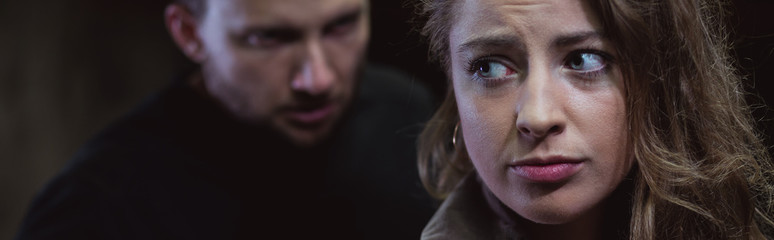 Fototapeta Aggressive man stalking scared girl