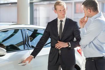 Salesman presenting auto to customer