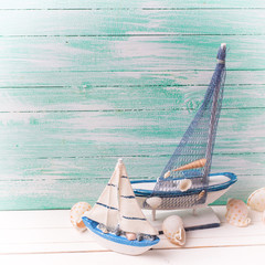Decorative sailing ships and marine items on wooden background.
