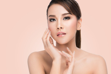 Spa Woman Portrait. Beautiful Asian Girl Touching her Face. Perfect Fresh Skin. Pure Beauty Model Female looking at camera. Youth and Skin Care Concept.on pink background with clipping path.