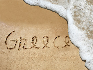 Conceptual Greece text in sand and water
