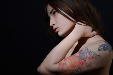 Beautiful asian woman with a tattoo on her arm and shoulder,dark