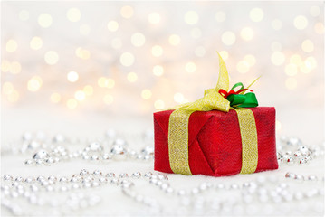 Red Christmas gift box with shiny golden ribbon and metalic beads. Bokeh with glow effect on white background. Copyspace for your greeting or wishes