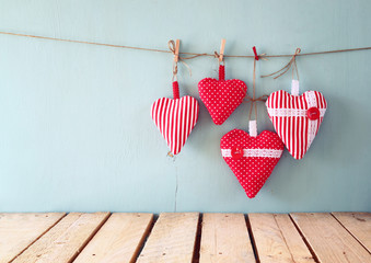 christmas image of fabric red hearts hanging on rope in front of blue wooden background. retro filtered