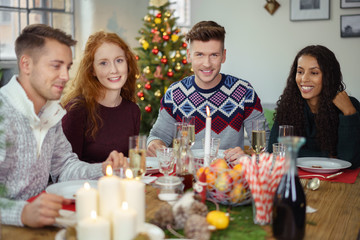 glückliche freunde sitzen beim gemütlichen weihnachtsessen am tisch