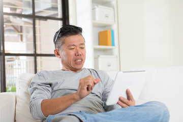 unhappy asian senior using tablet
