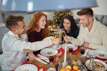 gäste beim weihnachtsessen stoßen mit sekt an