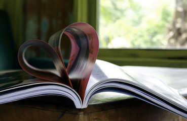 Heart from book pages in blurred background