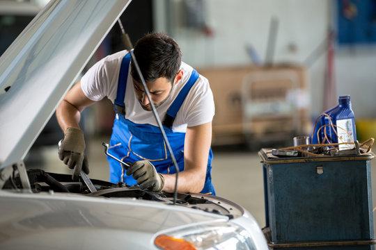 Auto mechanic working under the hood