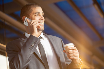 Successful afro businessman talking on mobile and smiling outdoo
