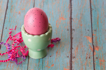 Pink Easter Egg in an Egg Holder on a textured background
