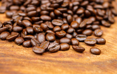 Roasted coffee beans on wood. (Arabica coffee)