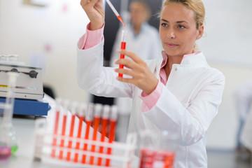 Chemist sampling liquid with pipette