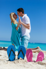 Slippers in sandy beach, travel concept