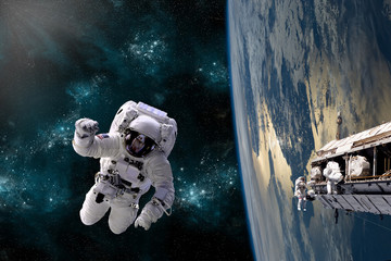 A team of astronauts perform work on a space station - Elements of this image furnished by NASA.