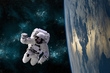 An astronaut floats in the zero gravity environment of space - Elements of this image furnished by NASA.
