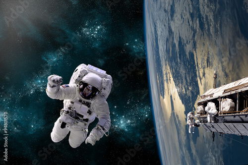 Wall mural A team of astronauts perform work on a space station - Elements of this image furnished by NASA.