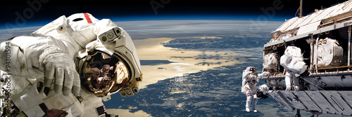 Wall mural A team of astronauts performing work on a space station.- Elements of this image furnished by NASA.
