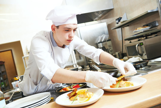 male cook chef decorating food on the plate