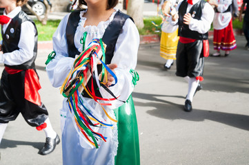 Girl with a typical regional dress playing a colored tambourine during a folkloristic show in Sicily