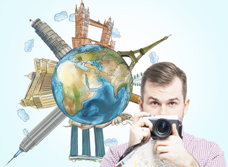A handsome tourist with camera and a globe with sketched famous places. Light blue background. Elements of this image furnished by NASA.