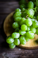 Vine of green grapes on rustic wooden background