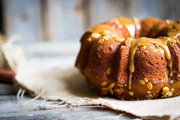 Homemade autumn cake with pumpkin seeds and caramel on wooden ba