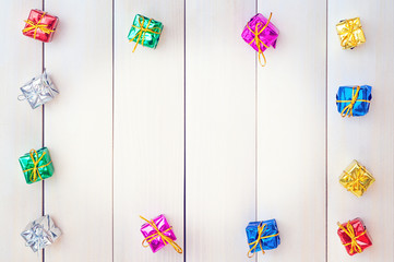 Boxes with gifts on a light wooden boards