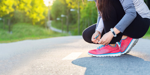 Female jogger tying her shoes
