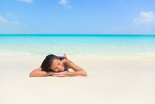 Relaxing woman on beach vacation sleeping on sand. Beautiful girl lying down under the sun tanning in perfect paradise white sand beach and pristine blue ocean background.
