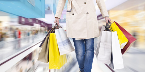 woman walking in shopping mall with paper bags