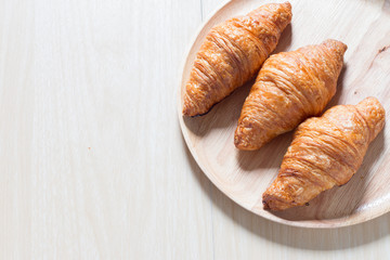 Croissant on wooden plate from above.