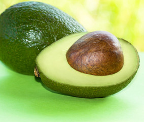 An Avocado cut in half on green surface.