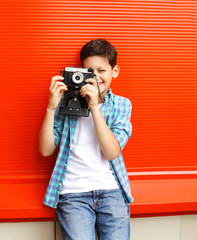 Happy little boy teenager with retro vintage camera in city over