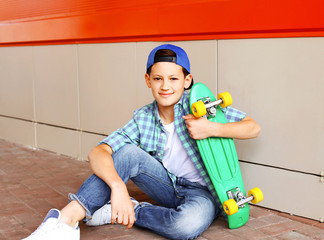 Portrait of stylish teenager boy with skateboard in city