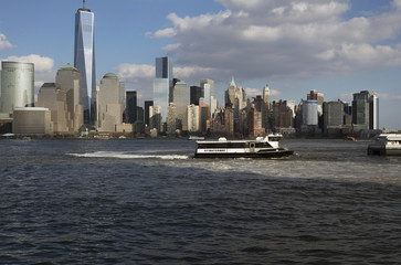 From New Jersey, a water taxi is seen in front of New York City Skyline featuring One World Trade...