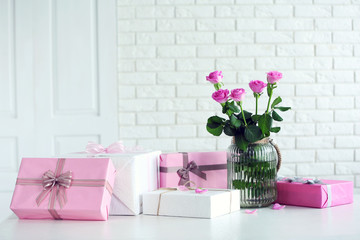 Composition of colourful gift boxes and flowers in glass on white table in front of brick wall background