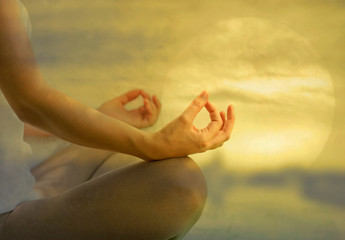 Yoga meditation peace, soul and mind zen balance concept. Young female in yoga posture meditating and making a zen symbol with her hands with beautiful sunset background.