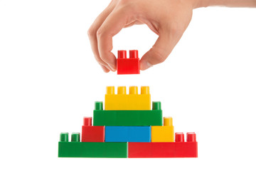 hand building up a wall by stacking up lego, business conception