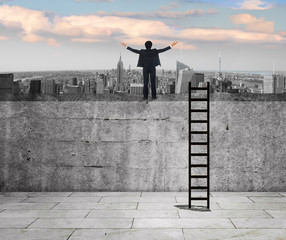 Success concept. Young businessman  looking ahead. Ladder leaning the wall and cityscape in the background