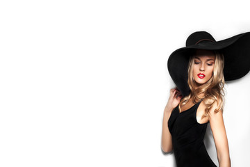 High fashion shot of blonde woman with curly hair in black hat and stylish elegant evening dress posing on white studio background.Red lips