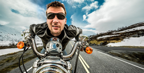 Wall Mural - Funny Biker in sunglasses and leather jacket racing on mountain